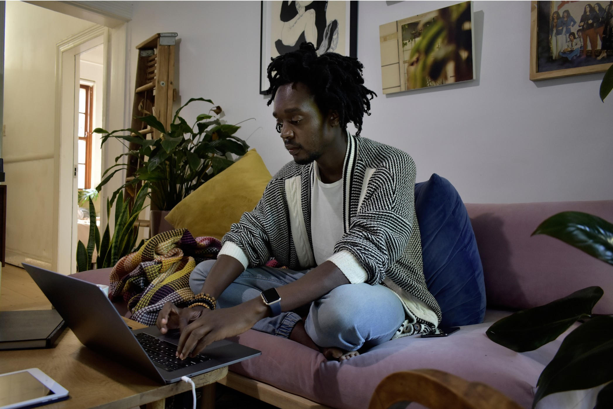 Black millennial with natural hair sitting on a couch and working from home t20 g LNL Pz